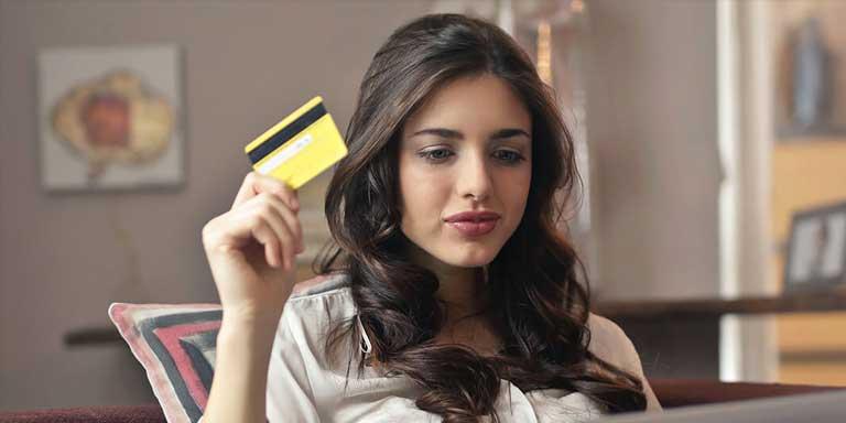 mulher sentada segurando o cartão altbank