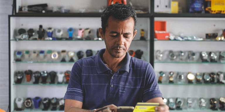 Homem em uma loja com celular e cartão de crédito altbank na mão