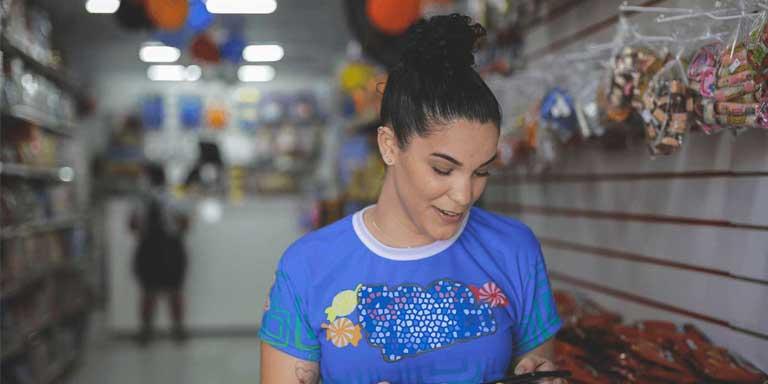 mulher em loja olhando aplicativo altbank