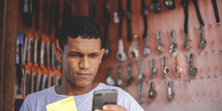 Homem em loja segurando cartão altbank e olhando no app altbank