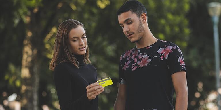 Clientes alt.bank em pé segurando cartão altbank