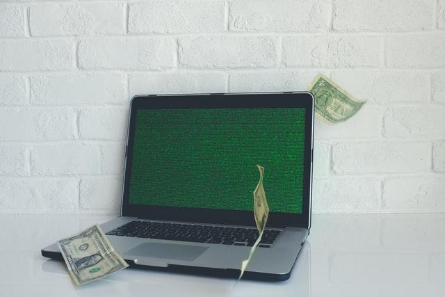 notebook em uma mesa branca com notas de dolares em volta