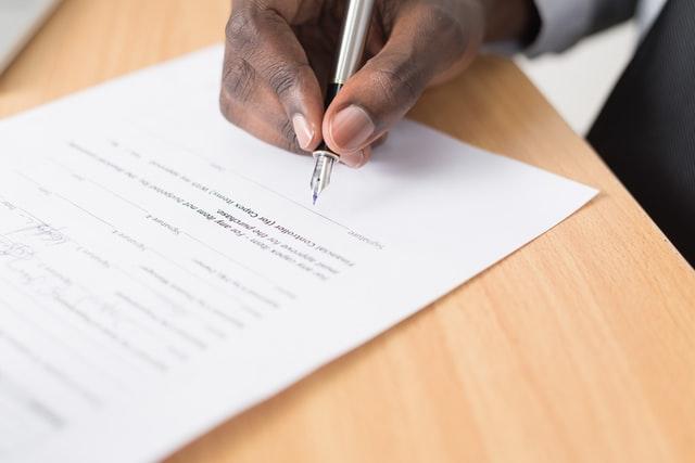 homem negro bom score assinando contrato de empréstimo