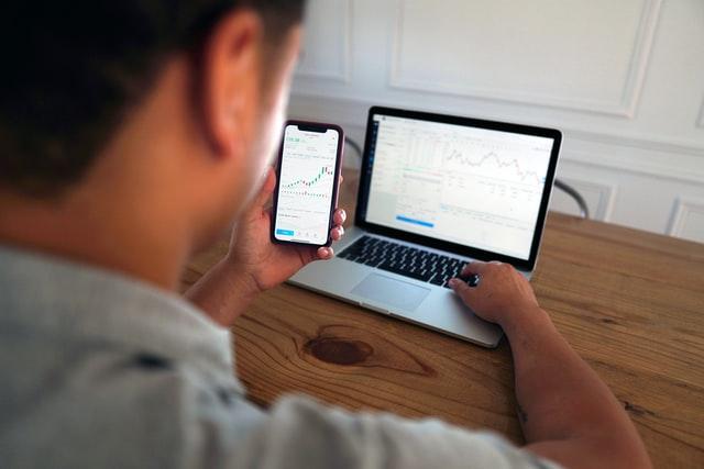 homem olhando aplicativo no celular e conta open banking