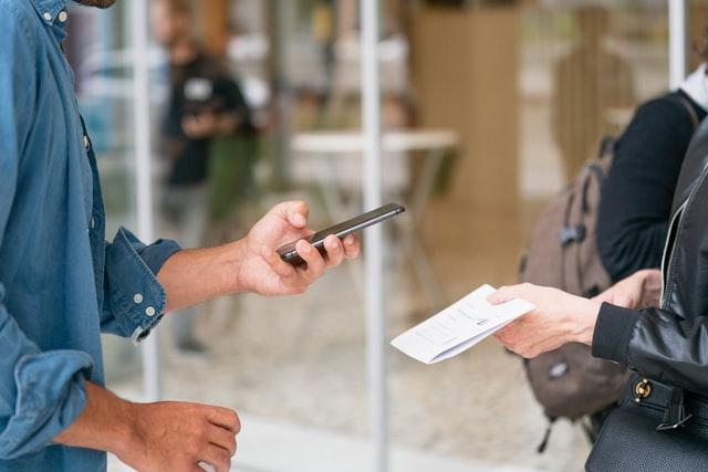 homem com celular na mão para pagar conta que uma mulher está segurando