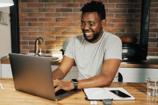 homem negro fazendo fazendo planejamento financeiro em uma mesa no notebook