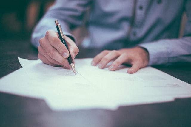 homem assinando contratos numa mesa