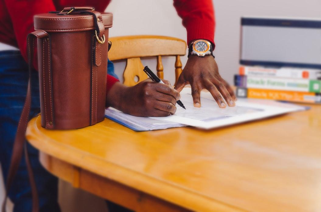 homem assinando contratos em uma mesa