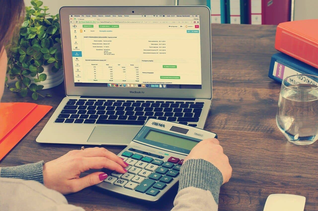 mulher com uma calculadora e notebook em uma mesa