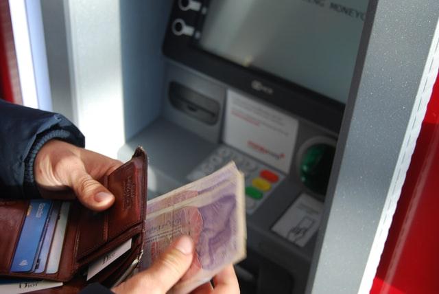 homem retirando dinheiro no caixa eletrônico