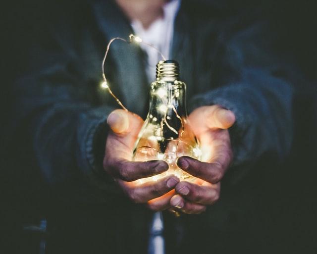 homem segurando lâmpada ligada ecomizando energia